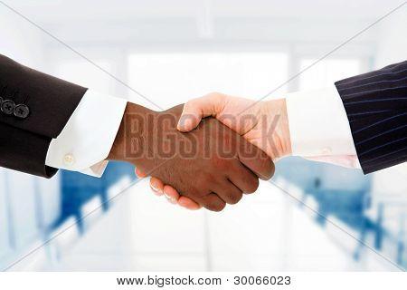 Closeup de multirracial aperto de mão entre dois homens de negócios, no escritório
