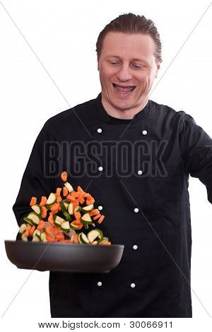 Smiling Cook Is Turning The Vegetables In A Pan