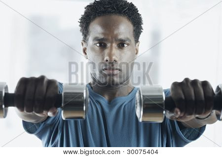 Portrait of man lifting weights