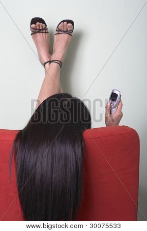 Rear view of woman in chair with cell phone