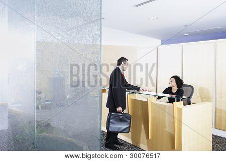 Businessman talking to receptionist