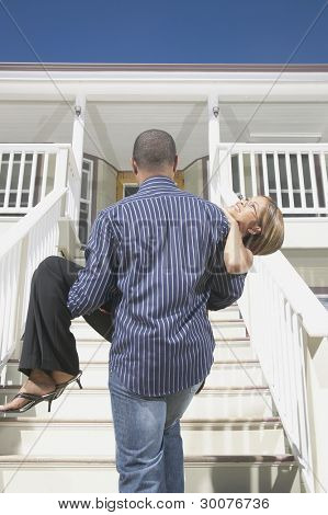Rear view of man carrying woman up stairs
