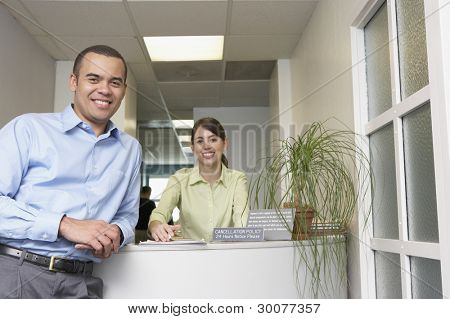 Portrait of male doctor and receptionist in office