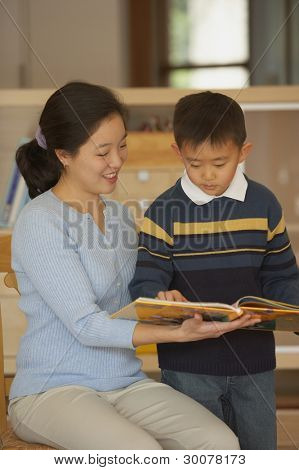 Female teacher reading book with student