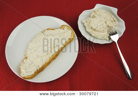 Bread of tuna spread on white plate, shell-shaped bowl in background