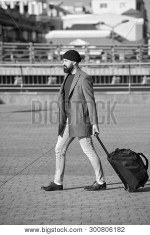 poster of Adjust Living In New City. Man Bearded Hipster Travel With Luggage Bag On Wheels. Traveler With Suit