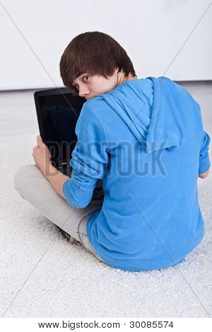 Surprised teenager boy caught surfing the web with forbidden content