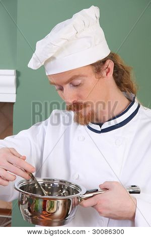 Young Chef Tasting Food With A Tablespoon