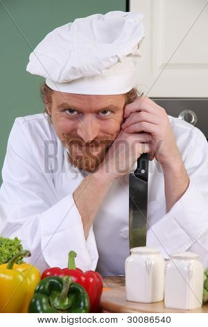 Funny Young Chef With A Knife In Kitchen