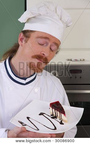 Funny Young Chef Smelling A Piece Of Cake