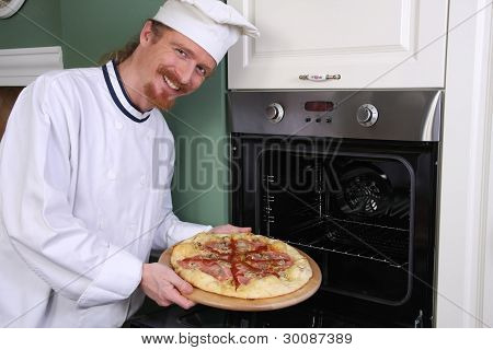 Young Chef With Italian Pizza In Kitchen