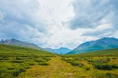 Spectacular View Of Distant Giant Mountains. Footpath Through Valley In Highlands. Hiking Path. Wond poster
