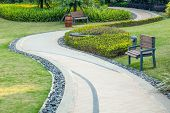 Beautiful summer garden with a walkway winding its way through. The curve walkway with stone tile on poster