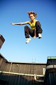 foto of parkour  - A young traceur in freefall while demonstrating the ability to react to challenges within the immediate environment in parkour - JPG