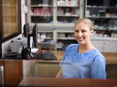 stock photo of medical office  - Young woman at work as receptionist and nurse in hospital looking at camera - JPG