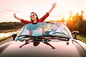 Traveling By Car - Happy Couple In Love Go By Cabriolet Car In Sunset Time poster