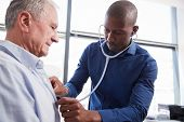 Doctor Listening To Chest Of Senior Male Patient During Medical Exam In Office poster