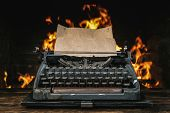 Typewriter With Blank Paper Page On A Writer Desk On A Burning Fire Background. poster