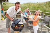 stock photo of chalet  - Family on vacation having barbecue - JPG