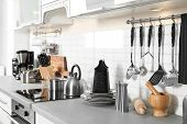 Different Appliances, Clean Dishes And Utensils On Kitchen Counter poster