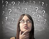 image of ignorant  - Woman with doubtful expression and question marks all over her head - JPG
