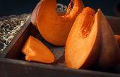 Fresh Juicy Pumpkin. Sliced raw Orange Pumpkin In A Vintage Wooden Pulp On A Table Against A Dark  poster