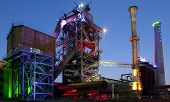 stock photo of blast-furnace  - steel industry blast furnace factory or plant abandoned old industrial architecture at night with colored lights Landschaftspark Duisburg - JPG