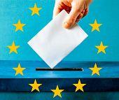 european Union parliament election concept - hand putting ballot in blue election box - EU flag poster