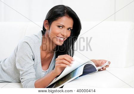 Smiling beautiful girl reading magazine and looking at camera at home
