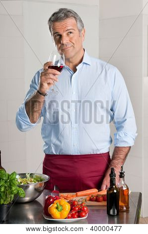 Mature man tasting a glass of red wine while cooking at home