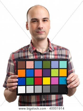 Man Holds An White Balance Card With Test Colors
