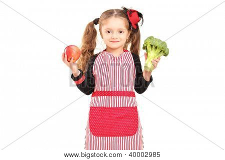A smiling girl with apron holding a broccoli and red apple isolated against white background