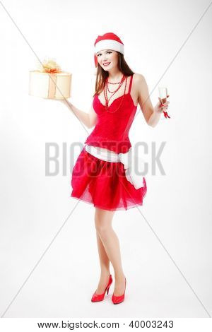 attractive woman in Xmas costume offers gift. studio shot