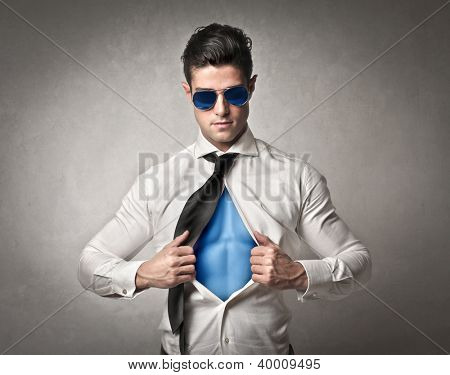Office worker with sunglasses opening his shirt like a superhero