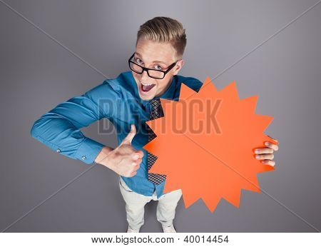 Awesome offer: Joyful salesman giving thumbs up for blank panel with space for text promoting sales isolated on grey background.