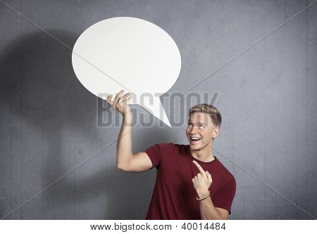 Fantastic idea: Laughing man pointing finger at white empty speech bubble with space for text, isolated on grey background.