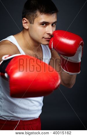 Portrait of young man in red boxing gloves looking at camera
