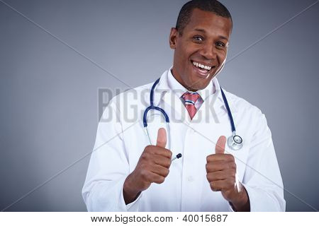 Portrait of confident doctor keeping thumbs up and looking at camera