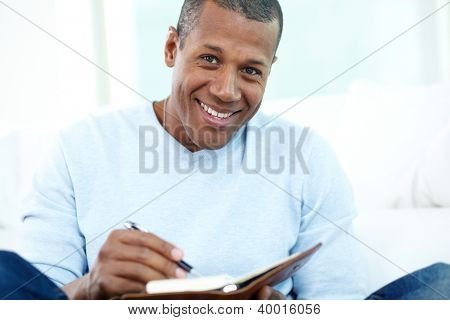 Image of young African man writing something in notepad