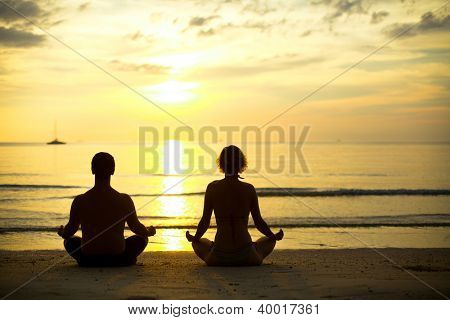 Yoga practice, a young couple sitting on the beach of the sea in the lotus position at sunset