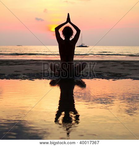 Yoga woman sitting in lotus pose on the beach during sunset, with reflection in water