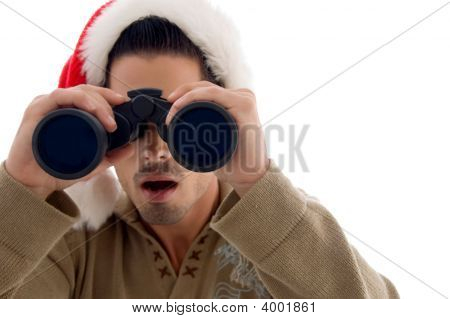 Handsome Guy Looking Into Binoculars Wearing Christmus Hat  And Surprised