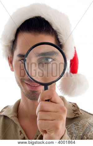 Male Looking Into Magnifier And Wearing Christmas Hat