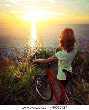 Woman standing on top of a hill with mountain bike and enjoying the sunset sea view