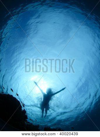 Unterwasser Shooting von einem Boden einer jungen Frau, die auf einer Meeresoberfläche Schnorcheln