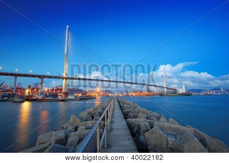 Port warehouse with containers and industrial cargoes , view under bridge on water break at sunset