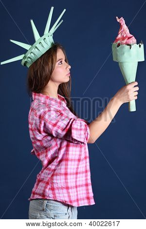 Beautiful girl in pink plaid shirt in crown holds and looks at torch - statue of liberty.