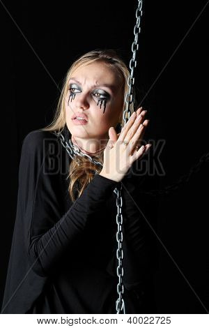 Melancholy zombie girl with black tears and cut throat holds chain and looks away at black background.