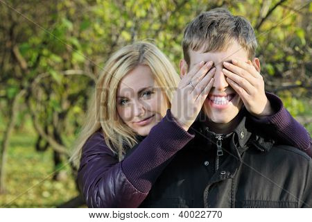 Young blonde woman covered eyes of smiling man by her hands in park at sunny autumn day. Focus on man.