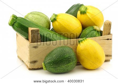 yellow and green zucchini (Cucurbita pepo) in a wooden crate on a white background